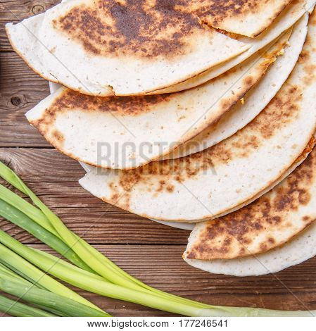 Tortillas with meat with green onions on wooden table
