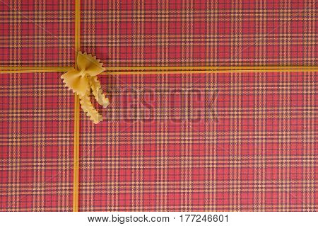 Pasta frame background. Pasta in shape of bow with ribbon on red checkered background. Top view