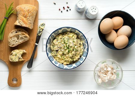 Homemade egg salad spread with mayonnaise mustard red onion sprinkled with chives top view background on white table.