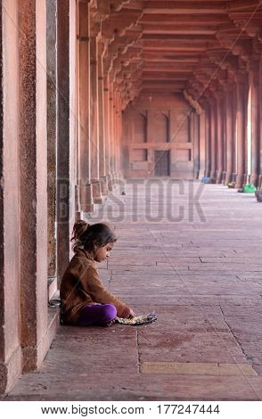 FATEHPUR SIKRI, INDIA - FEBRUARY 15: A poor girl eating in Fatehpur Sikri complex, Uttar Pradesh, India on February 15, 2016.