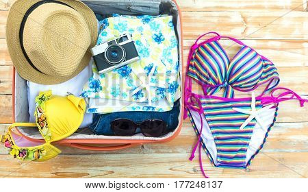 Open the suitcase with tourist things: women's hat swimsuit camera denim shorts dresses sunglasses perfumes nail polish mobile phone tablet on wooden background