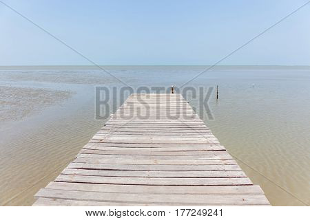 Old wooden bridge to the sea tranquil scene for traveling and relaxation.