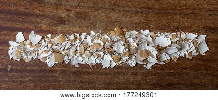 Pieces of eggshell. Many tiny details of eggshell , wood background. Egg shell in the form of a thick line