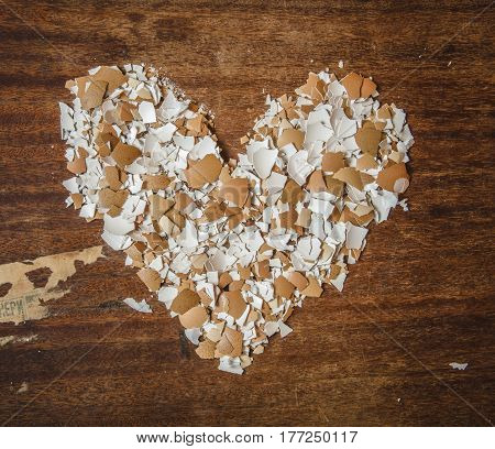 Pieces of eggshell. Many tiny details of eggshell , wood background. Eggshell in the form of heart