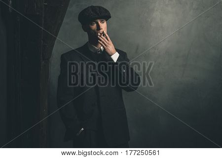 Retro 1920S English Gangster Smoking A Cigarette. Wearing Suit And Flat Cap.