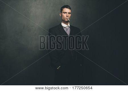 Retro 1920s english gangster smoking a cigarette.