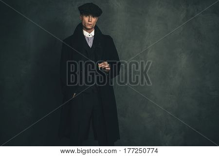 Macho Retro 1920S English Gangster Wearing Black Coat And Flat Cap Holding Cigarette.