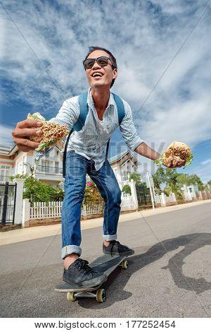 Funny man skating and try to eat hamburger