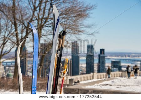 Skis in snow with Montreal skyline in the distance