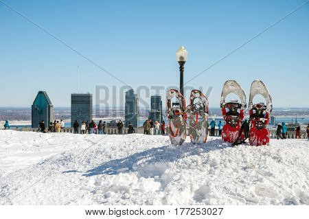 Snowshoes in snow with Montreal skyline in the distance