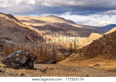The picturesque autumn landscape with mountains covered with snow winding river rocky road and golden trees on a background of the sky and clouds