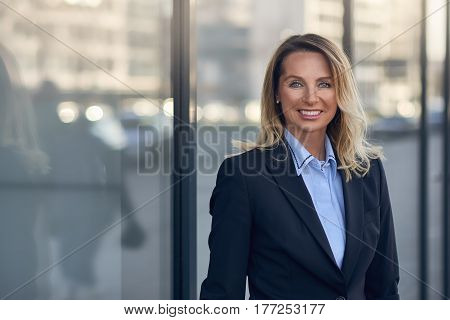 Smiling Businesswoman In Front Of A Glass Window