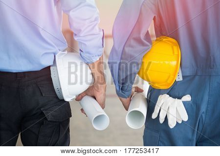 Close up back view of male construction worker and Asian civil engineer holding roll of drawing and safety helmet indoor of construction site.