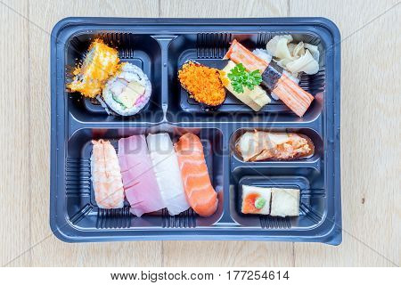 Top view of bento to-go plastic box mixed nigiri and assorted sushi roll in lunch box place on wooden background.