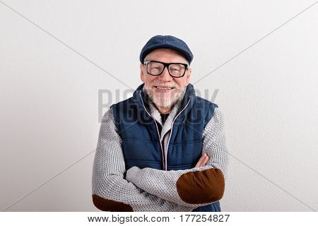 Handsome senior man in gray sweater, blue vest jacket, black eyeglasses and flat cap smiling, eyes crossed. Studio shot against white wall.