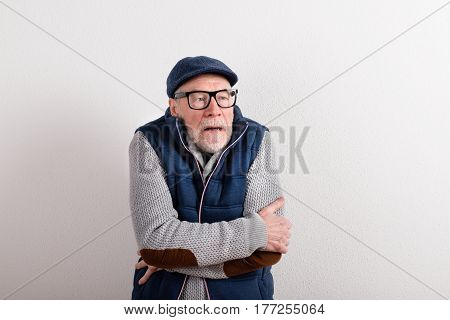 Handsome senior man in gray sweater, blue vest jacket, black eyeglasses and flat cap smiling, eyes crossed, being cold. Studio shot against white wall.