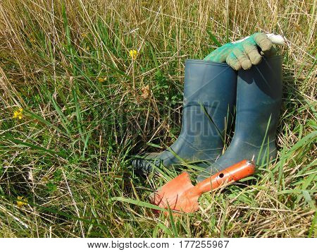 Garden work / rubber boots in grass with small shovel