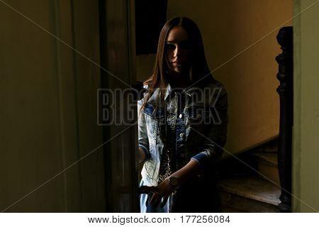 Emotional portrait of girl at door. Beautiful mysterious brunette in dark room