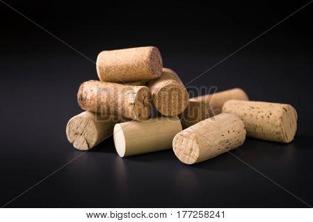 Many wine corks on a dark background.