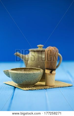 Ceramics bowl and chasen - special bamboo matcha tea whisk lying on blue wooden background