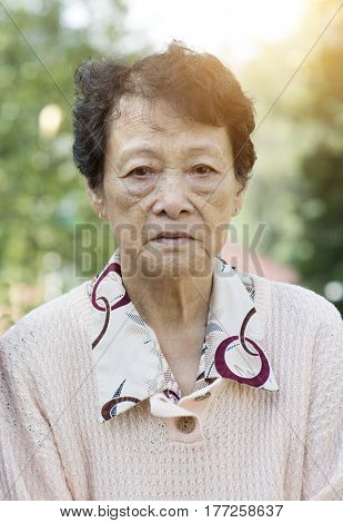 Portrait of upset Asian senior adult woman at outdoor garden park in the morning.