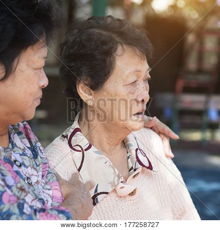 Candid shot of Asian senior adult women chit chatting at outdoor park in the morning.