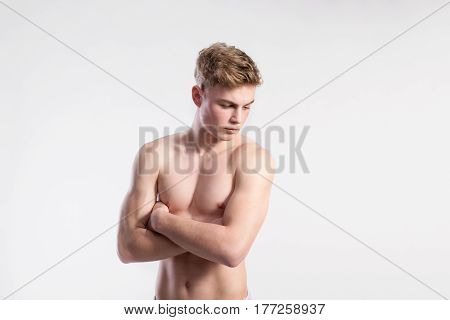 Handsome shirtless fitness man, arms crossed. Studio shot on gray background.