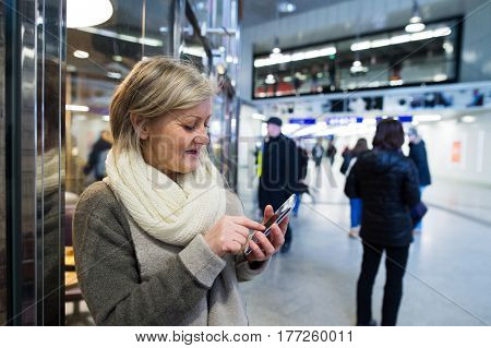 Beautiful senior woman in the hallway of subway in Vienna, holding a smart phone, texting