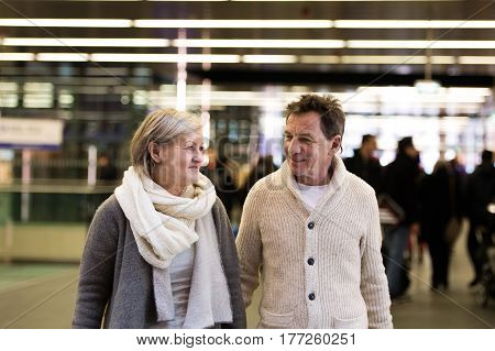 Beautiful senior couple walking in the crowded hallway of subway in Vienna, holding hands.