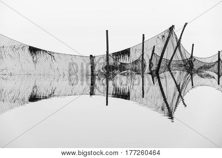 Fishing net reflected in seawater in a foggy day