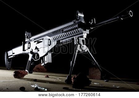 Semi automatic rifle on a bipod with a dark background