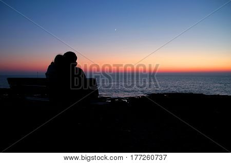 Couple sits on a bench and waits for the sunrise