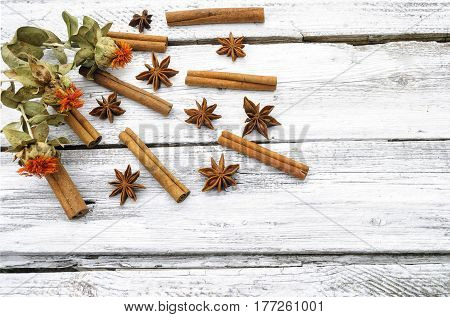 Cinnamon, anise and saffron on a white wooden surface