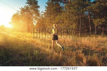 Young sporty girl running on a field near the trees at sunset in summer. Athlete running on the off road in the evening. Active woman. Sport and healthy lifestyle. Jogging fitness. Woman runners