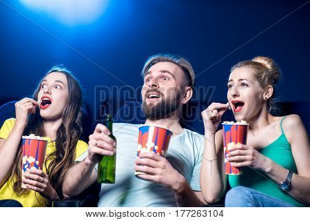 Shocked friends watching film sitting together with popcorn in the cinema