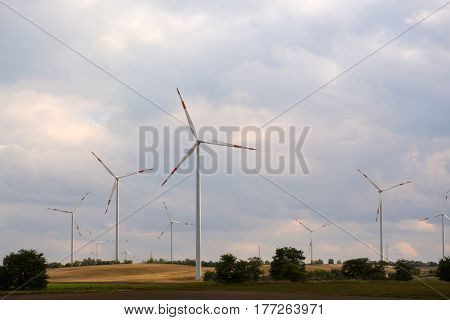 Wind turbine farm electric power generators on field on cloudy sky background. Renewable energy production