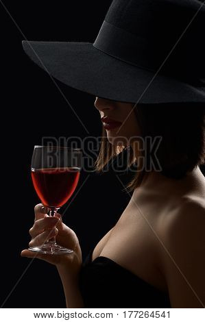 Red wine. Vertical portrait of a mysterious woman in a hat hiding her face having a glass of red wine in a dark room with mysterious lighting incognito secret night evening luxury winery concept