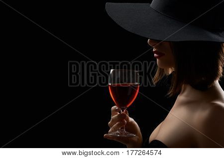 Drink of gods. Horizontal shot of a sexy woman in a black dress and a hat hiding her face drinking red wine on black background copyspace mysterious drink alcohol celebration anniversary anonymous