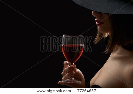 In love with wine. Cropped studio close up of a woman in a hat hiding her face holding a glass of red wine copyspace sexy hot lips seductive mysterious dark artistic shadow lighting