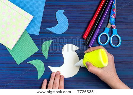 Making a greeting card for Mother's Day. Children's art project. DIY concept. Step-by-step photo instruction. Step 5. Application of glue to the detail of image