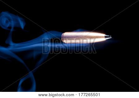 Copper plated bullet on black with blue smoke behind