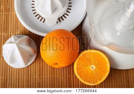 The fruit juicer and oranges on mat