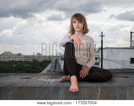 Teenage girl sitting high on the roof of the house