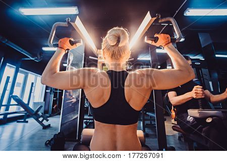 Young Woman Athlete With An Active Lifestyle Pulls On The Training Appliance For The Arms, Chest And