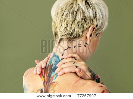 Woman shirtless with tattoo on background