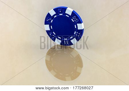 On the reflective surface is a blue casino chip