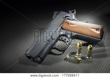 Semi automatic pistol and cartridges on a dark rubber mat