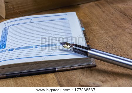 On the wooden surface is an open diary and fountain pen