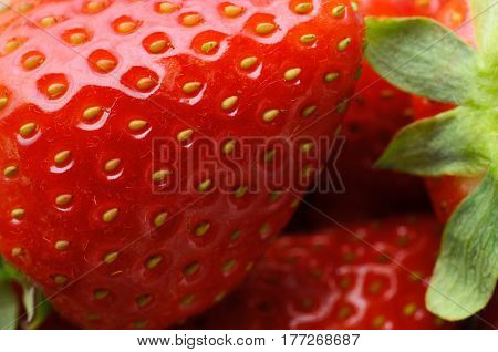 Close up (macro) of fresh red strawberries showing texture partial outline and leaves.