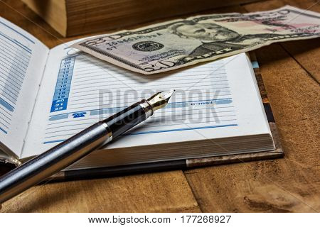 On the wooden surface is an open diary a fountain pen and a money bill